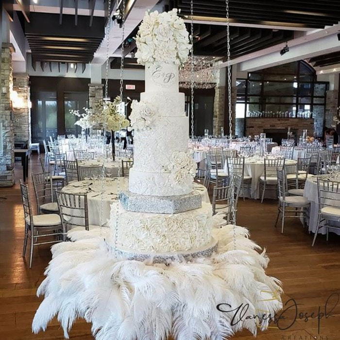 white and silver wedding cake on a hanging table with white feathers