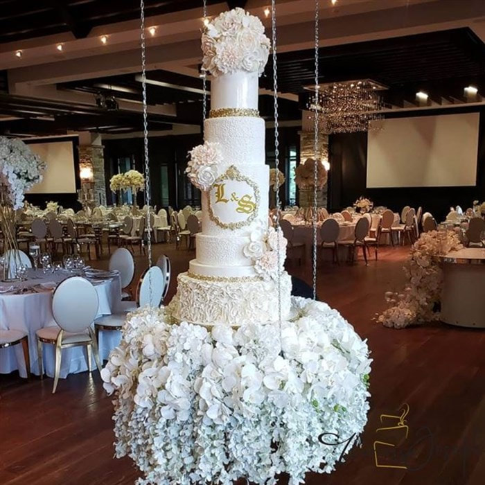 white and gold royal theme wedding cake on a hanging table with flowers