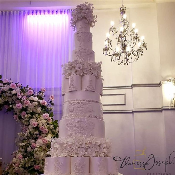 Very tall all white wedding cake  with white flowers tiers