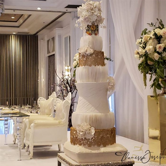 textured white wedding cake with gold lace