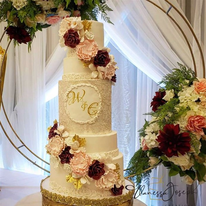 White wedding cake with pink, burgundy and gold flowers