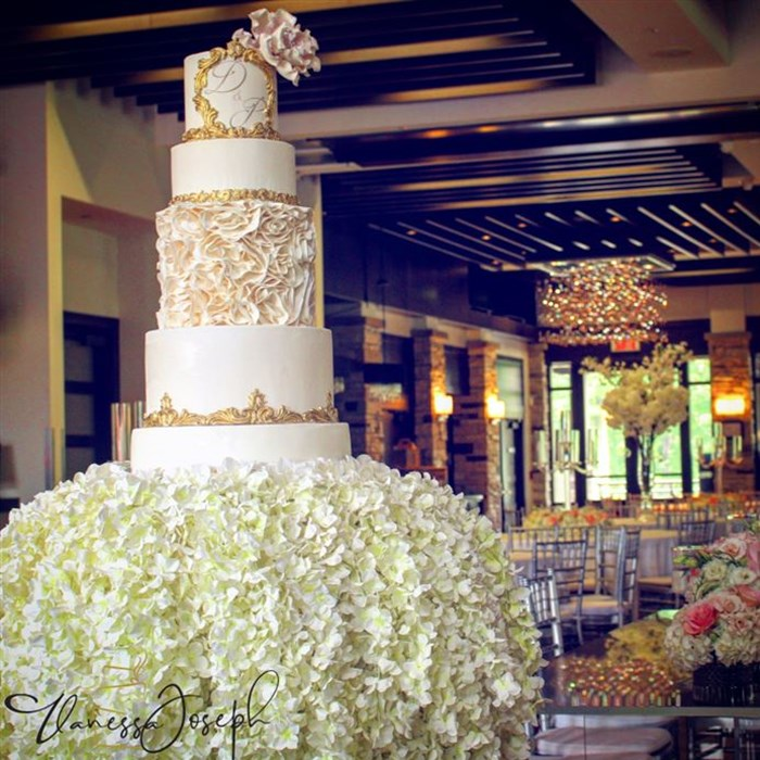 Royal white and gold wedding cake on a cascade of flowers