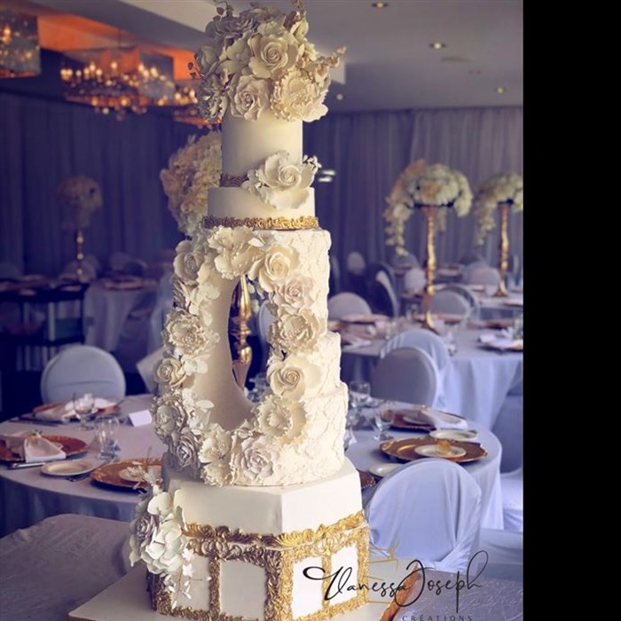 Extravagant white and gold wedding cake with a hole in the middle