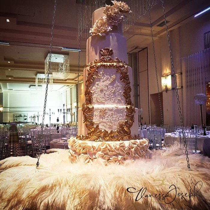 royal white and gold wedding cake on hanging table with white feathers