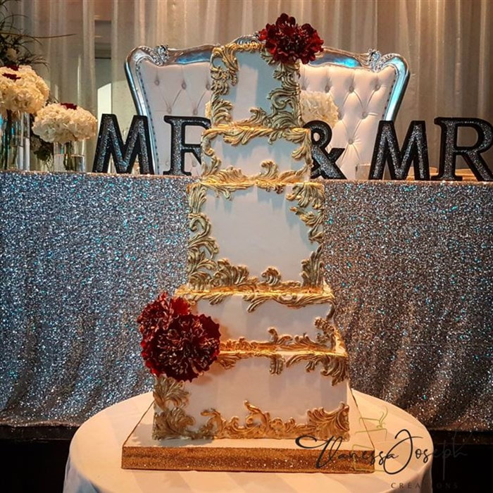 Square baroque white and gold wedding cake with burgundy flowers