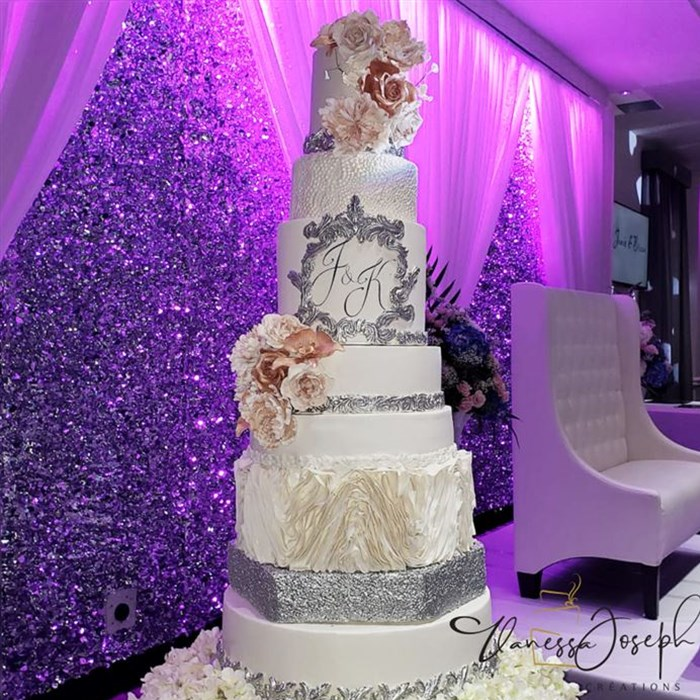 White and silver wedding cake with pink flowers