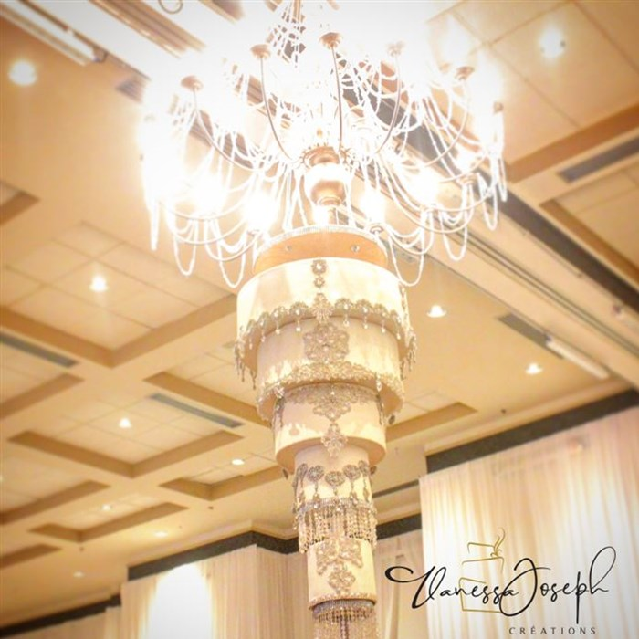 Upside down white and diamant wedding cake hanging from a chandelier