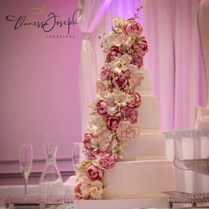 White wedding cake with cascades of fuchsia pink, pale pink and white flowers
