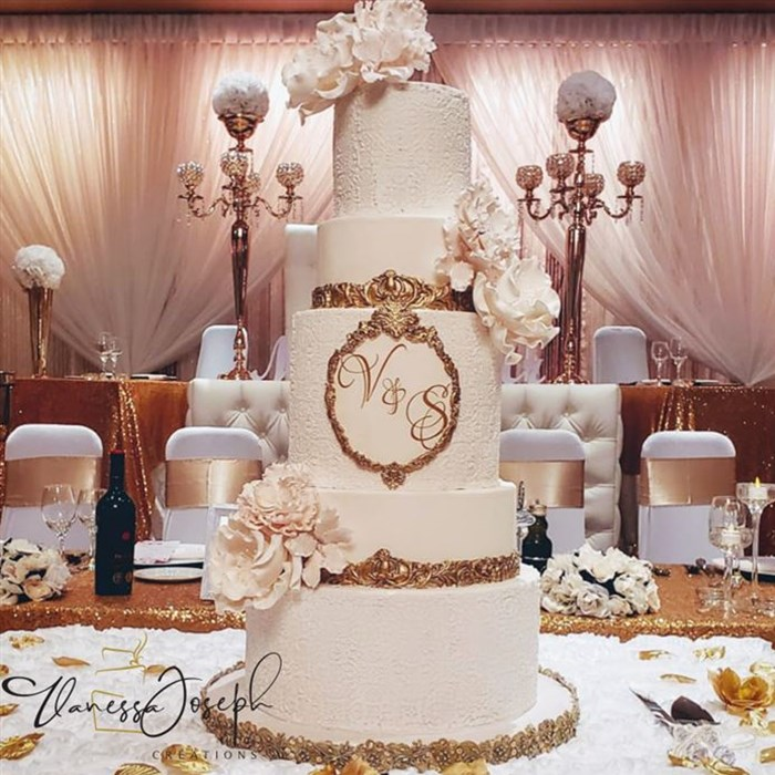 white and gold wedding cake with white flowers
