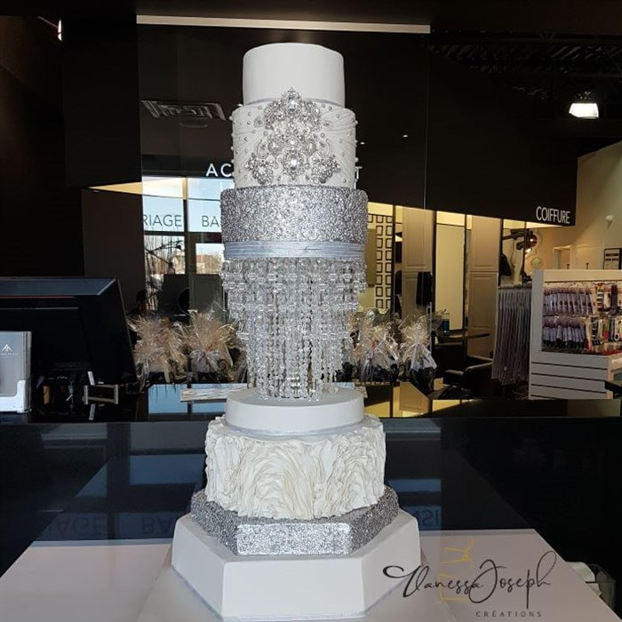 white and silver wedding cake with integrated chandelier