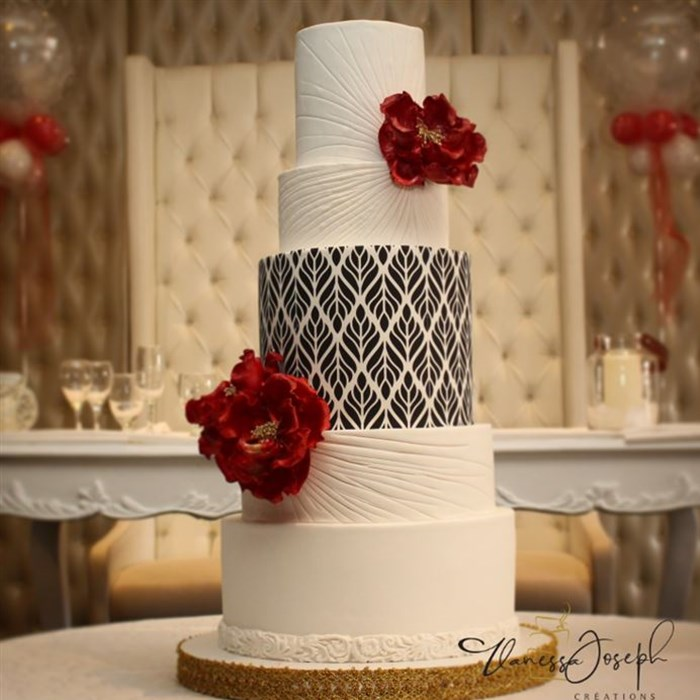 white wedding cake with black and white pattern and bright red flowers