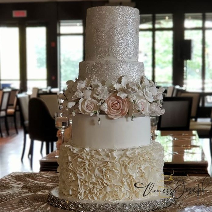 white and cream wedding cake with lace and flowers