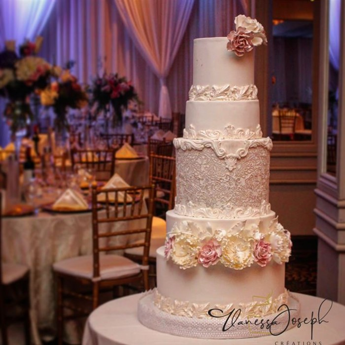 white wedding cake with lace and flowers