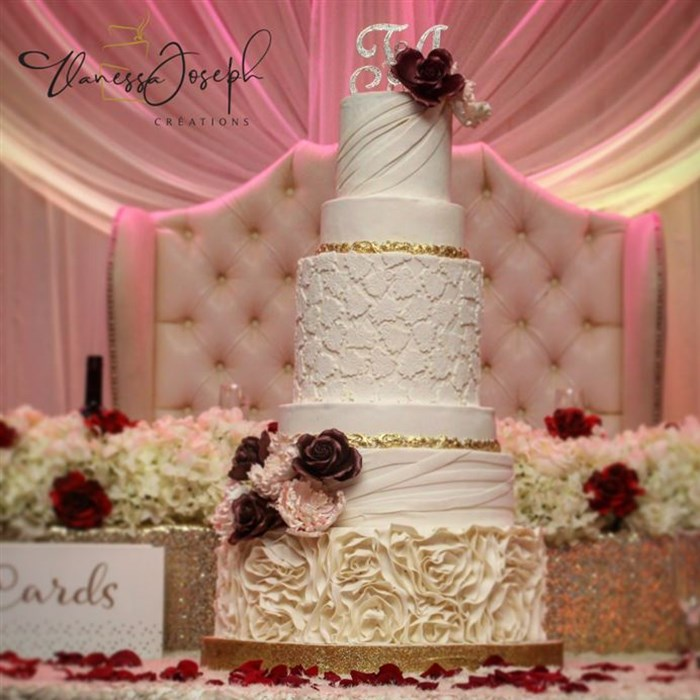 romantic white and gold wedding cake with pink and burgundy flowers