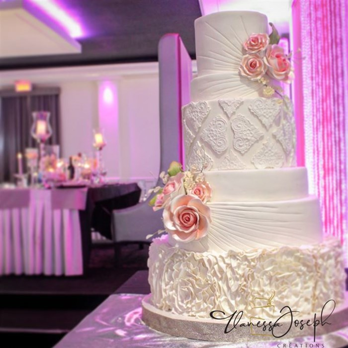 Textured white wedding cake with pink flowers