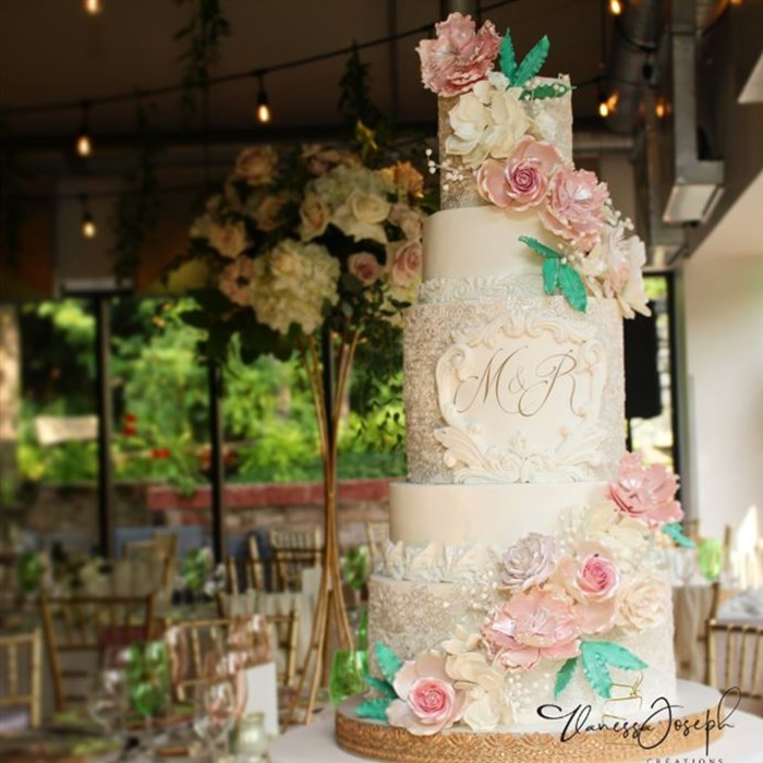 Garden white wedding cake with pink and white flowers and green leaves