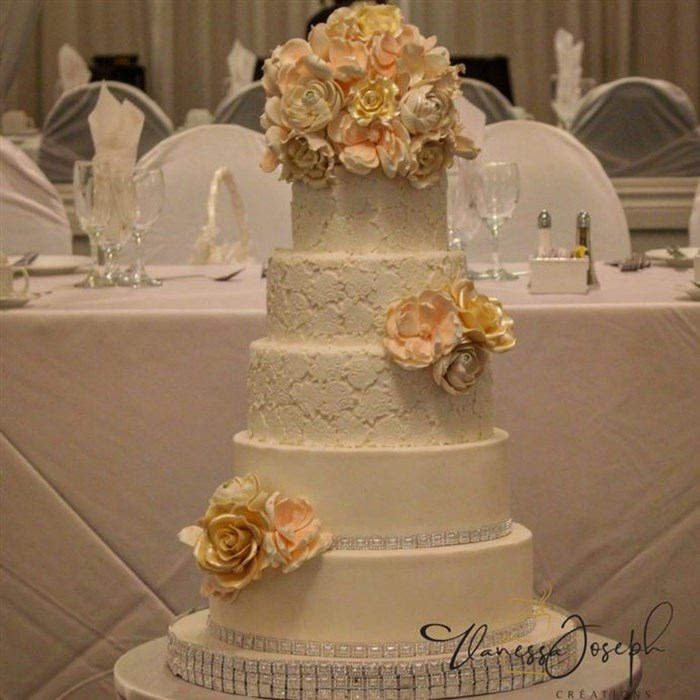 romantic white wedding cake with lace and pastel colors flowers