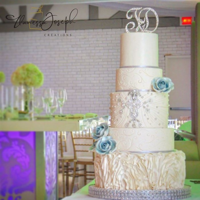 white wedding cake with blue flowers and silver jewelry