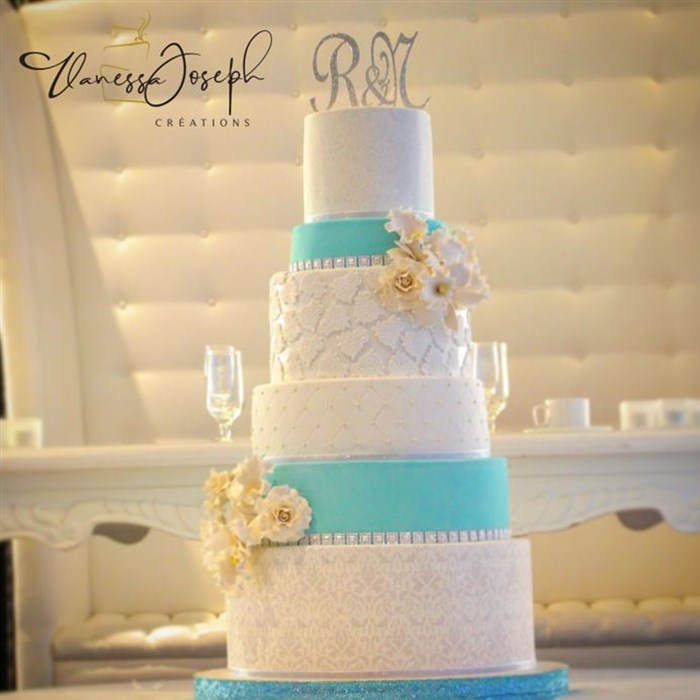white and turquoise wedding cake with white and yellow flowers