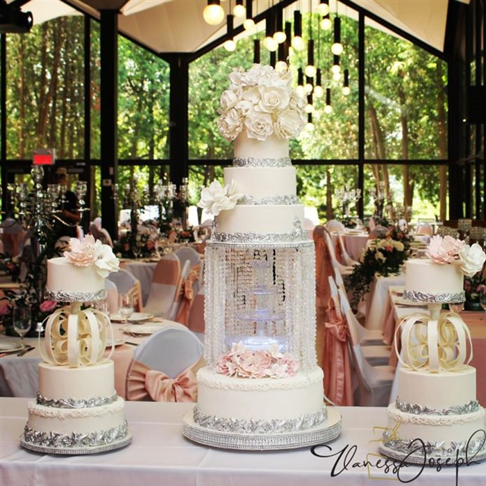 Trio of white and silver wedding cake with pink flowers, integrated half chandelier with fountains, nod to the 80s