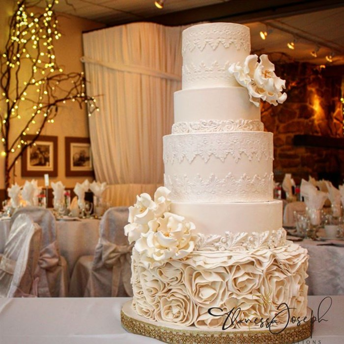 romantic white wedding cake with lace and flowers