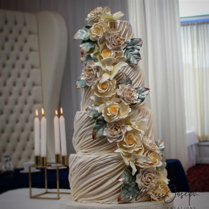Draped white wedding cake with white and yellow cascaded flowers