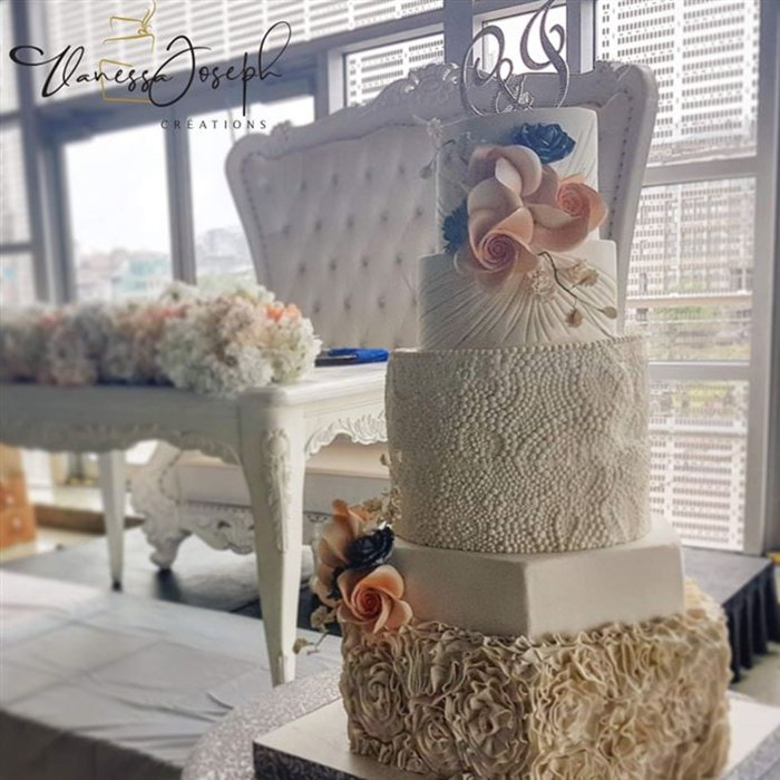 white wedding cake with peach and royal blue flowers
